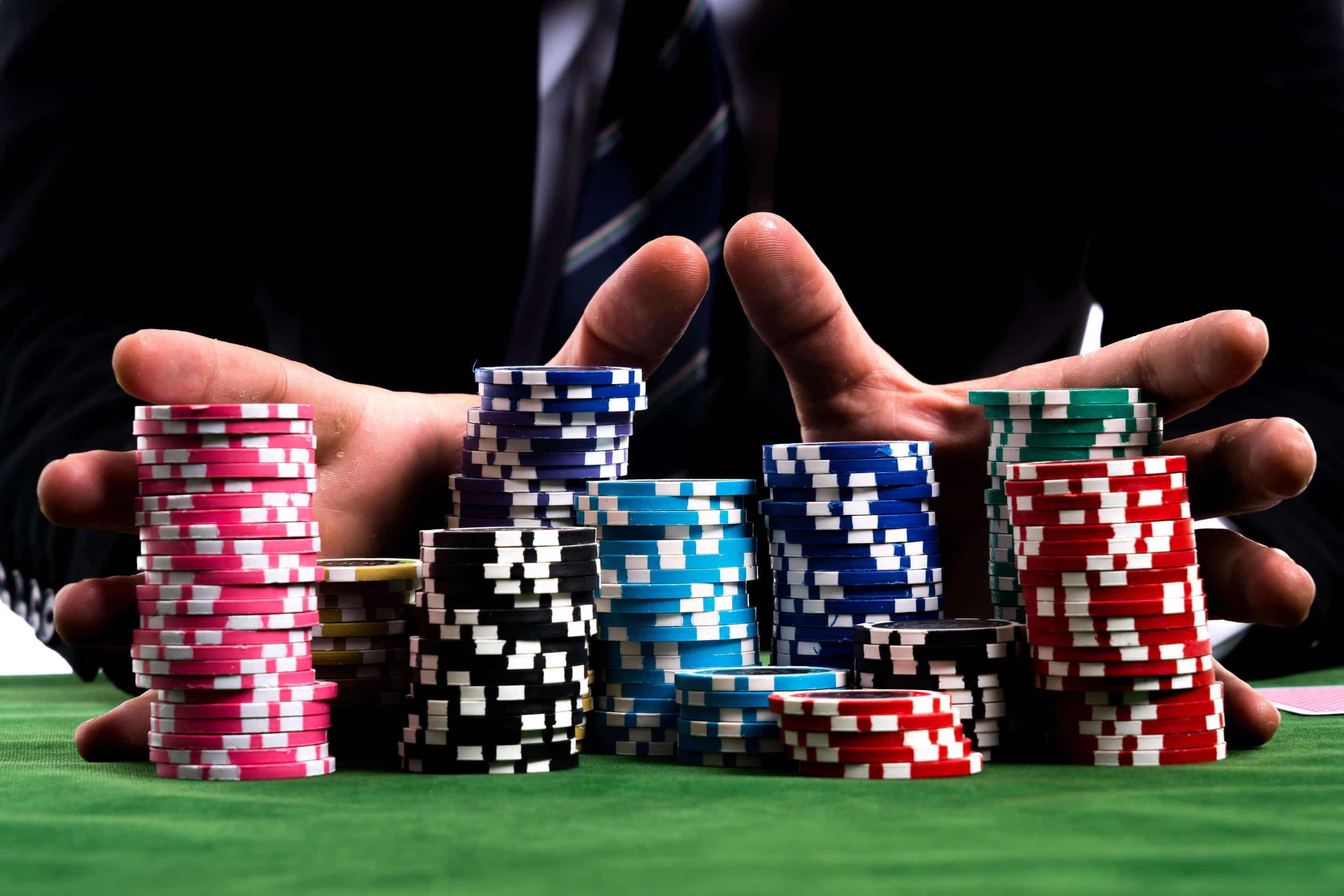 a pair of hands holding a big pile of poker chips