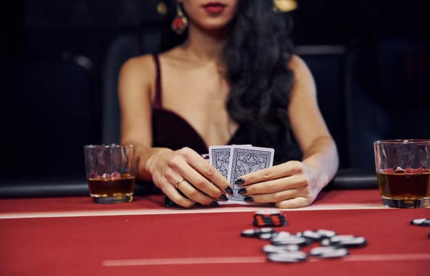 a woman with long black ahir holding casino cards in her hands with poker chips next to her
