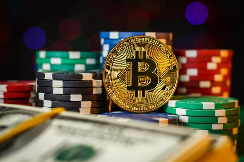 bitcoin laying next to poker chips on a table
