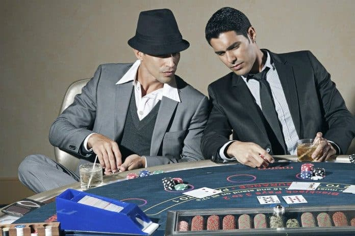 two men sitting in front of a poker table