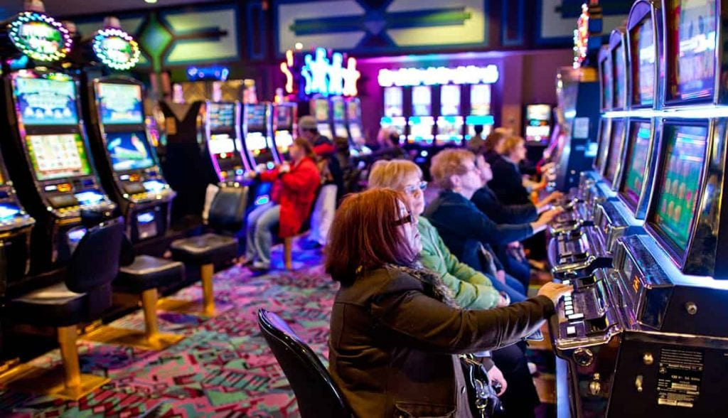 a group of elderly women playing the slots